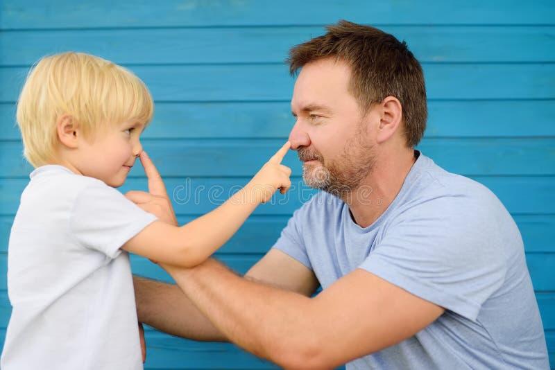 逗人喜爱的小男孩和他的父亲按了在彼此的鼻子的手指 免版税库存图片