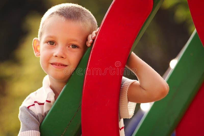 逗人喜爱的小男孩在一个五颜六色的孩子操场 免版税库存图片