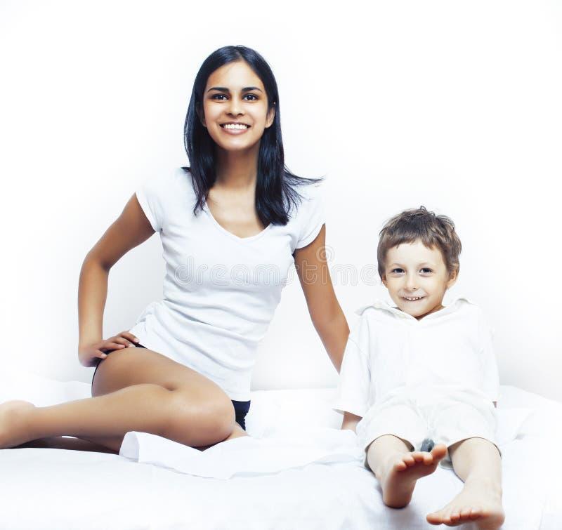 逗人喜爱的小男孩在与母亲的床上有的睡衣的乐趣愉快微笑,生活方式人概念 免版税库存照片