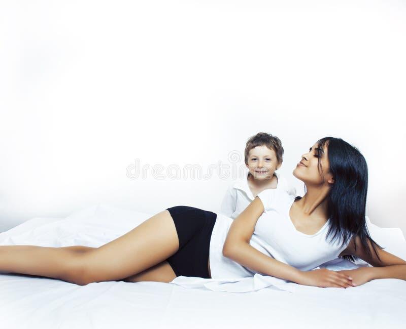 逗人喜爱的小男孩在与母亲的床上有的睡衣的乐趣愉快微笑,生活方式人概念 库存图片