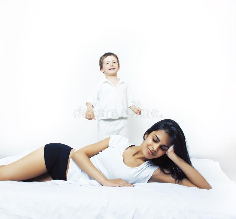 逗人喜爱的小男孩在与母亲的床上有的睡衣的乐趣愉快微笑,生活方式人概念 图库摄影