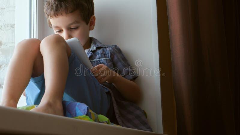 逗人喜爱的小男孩在家使用在窗台的一台白色片剂个人计算机 免版税库存照片
