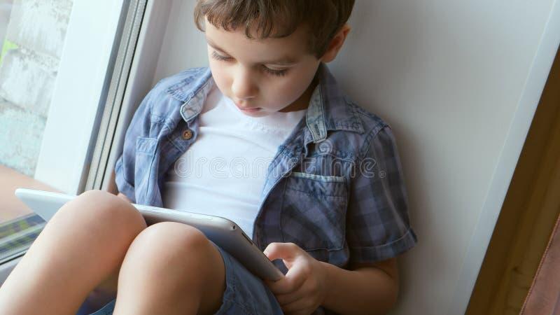 逗人喜爱的小男孩在家使用在窗台的一台白色片剂个人计算机 库存图片
