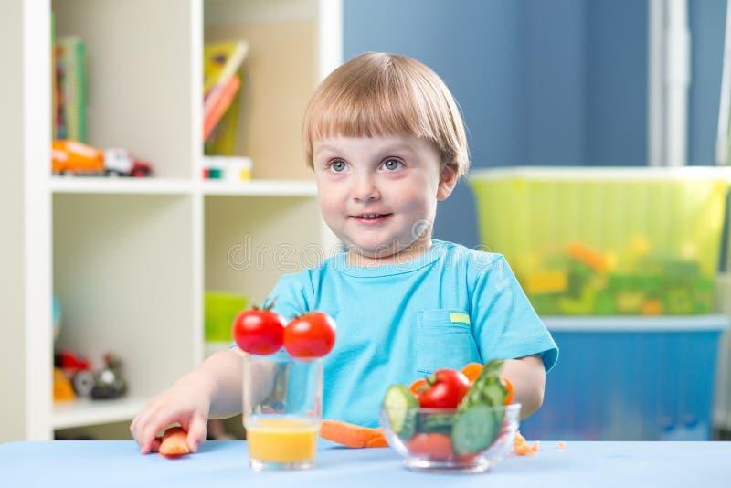 逗人喜爱的小男孩在屋子里吃红萝卜和其他菜 图库摄影