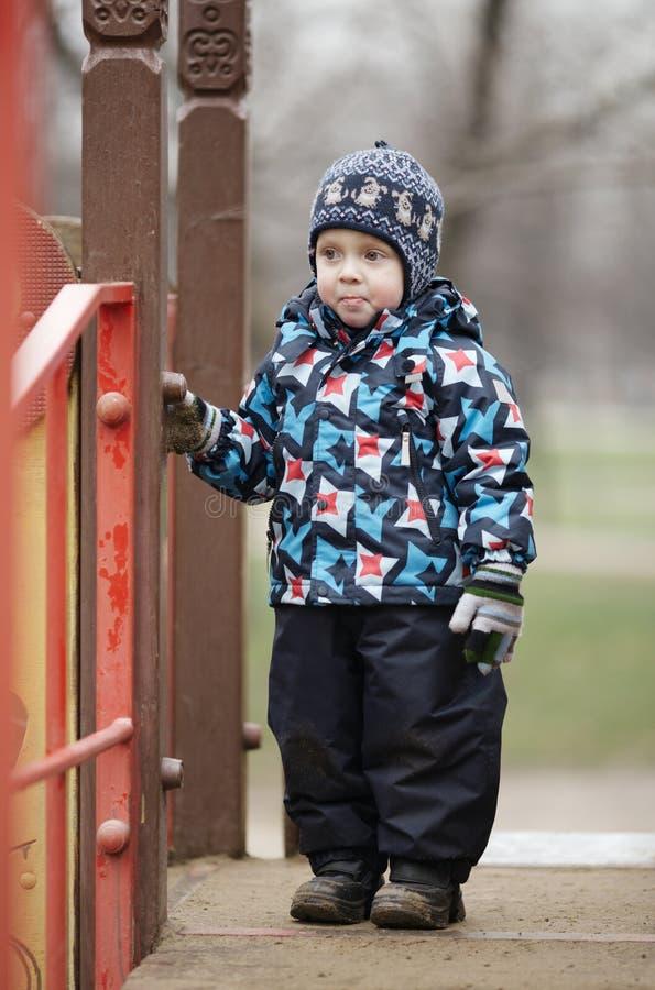 逗人喜爱的小男孩在时髦冬天衣裳穿戴了 库存图片