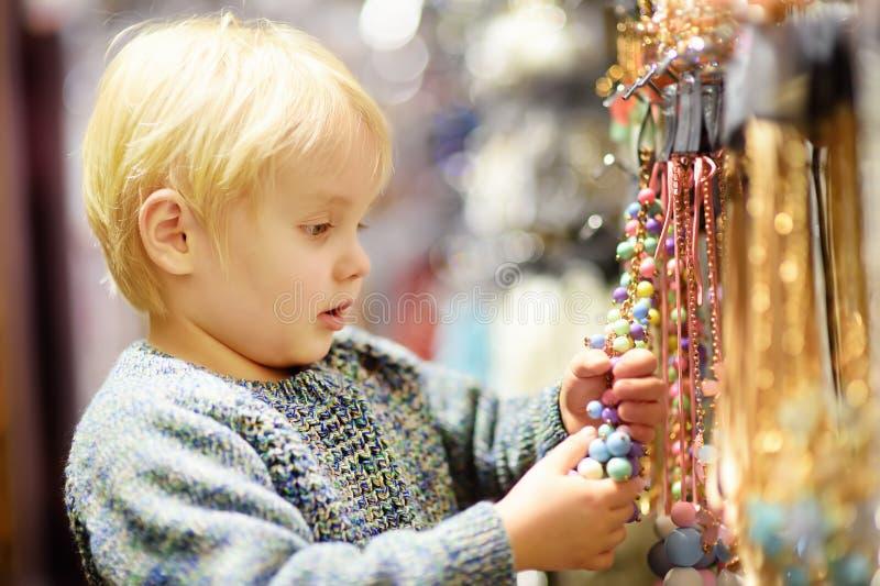 逗人喜爱的小男孩在辅助部件商店帮助他的妈妈选择首饰 库存图片