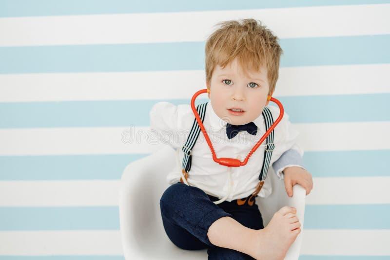 逗人喜爱的小男孩年轻人医生Using Toy Stethoscope 库存图片