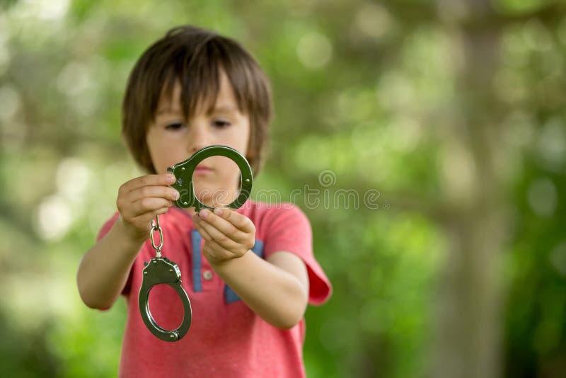 逗人喜爱的小男孩用手在他的手上打 库存照片