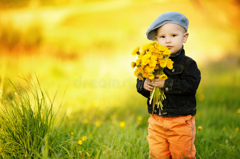逗人喜爱的小男孩用蒲公英 图库摄影