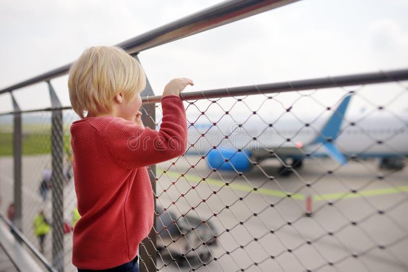 逗人喜爱的小男孩看看在观察台的飞机在小欧洲镇机场在飞行前的 迷人的孩子乘客 图库摄影