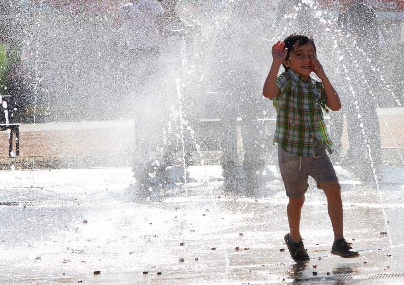 逗人喜爱的小男孩笑并且获得跑在喷泉下的乐趣 库存照片