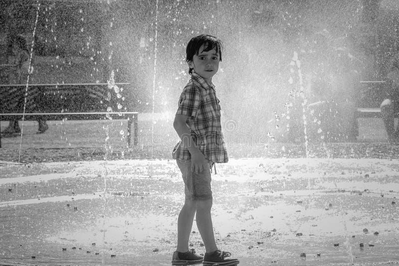 逗人喜爱的小男孩笑并且获得跑在喷泉下的乐趣 免版税库存照片
