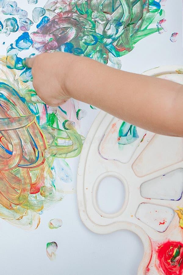 逗人喜爱的小男孩绘画用使用笨拙的油漆的油漆手 皇族释放例证