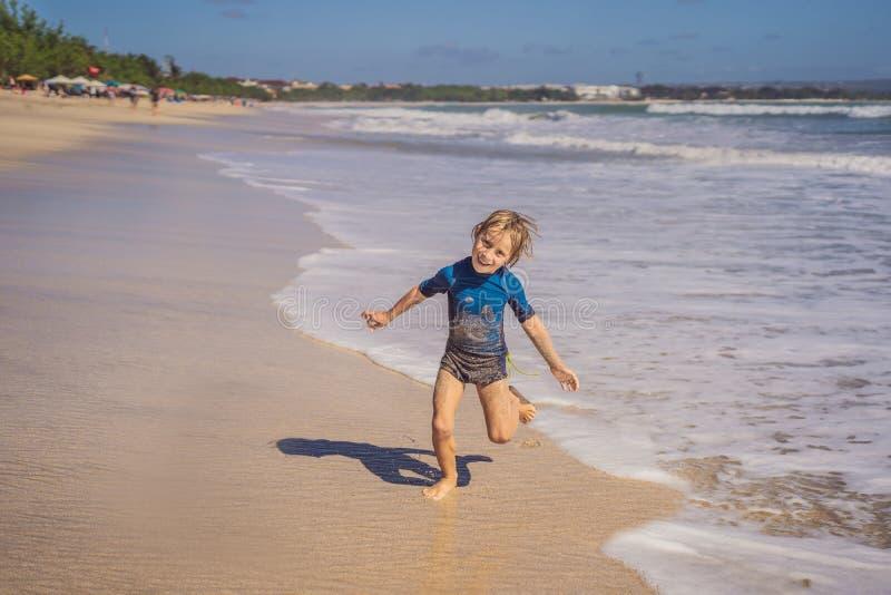 逗人喜爱的小男孩获得在热带海滩的乐趣在暑假时 库存照片