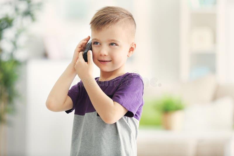 逗人喜爱的小男孩谈话用电话 免版税库存图片