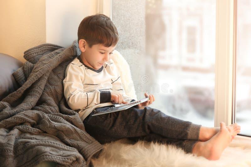 逗人喜爱的小男孩阅读书,当坐窗口基石时 免版税库存图片