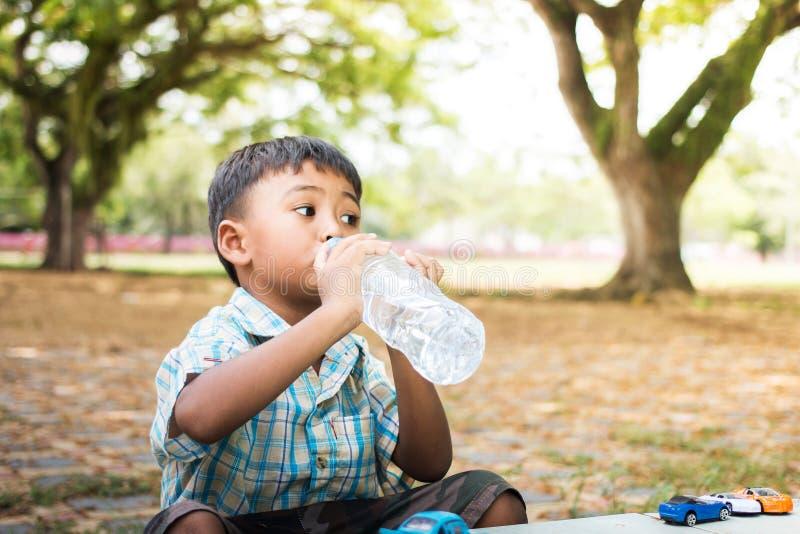 逗人喜爱的小男孩饮用水在绿色公园,焦点手 免版税库存图片