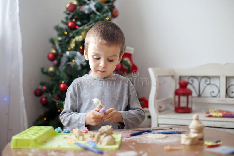 逗人喜爱的小男孩,使用与塑造面团,铸造在家计算 免版税图库摄影