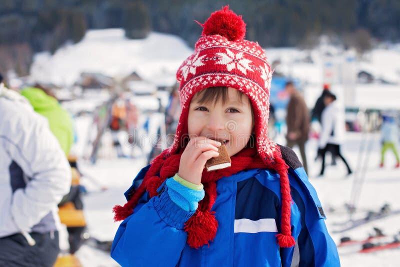 逗人喜爱的小男孩,愉快地滑雪在奥地利滑雪胜地在mo 图库摄影