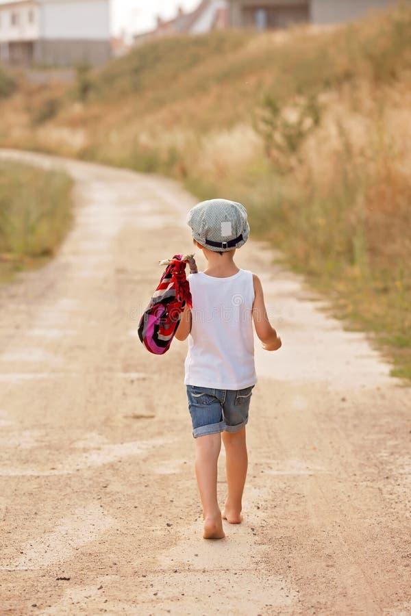 逗人喜爱的小男孩,拿着捆绑,吃面包和微笑, wa 免版税图库摄影