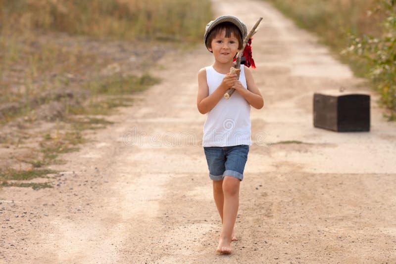 逗人喜爱的小男孩,拿着捆绑,吃面包和微笑, wa 免版税库存图片