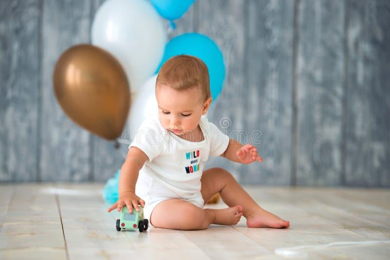 逗人喜爱的小男孩1岁坐一个温暖的木地板并且使用与玩具汽车 在计划生日气球后 库存照片