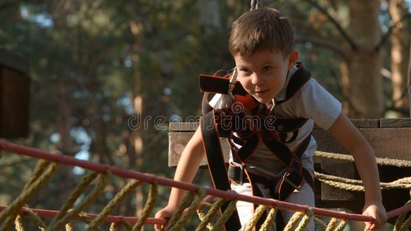 逗人喜爱的小男孩画象在一座索桥走在冒险绳索公园 库存图片