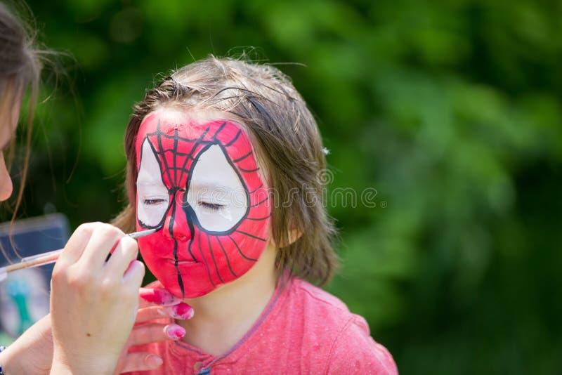 逗人喜爱的小的五岁男孩,安排他的面孔被绘作为spid 免版税库存照片