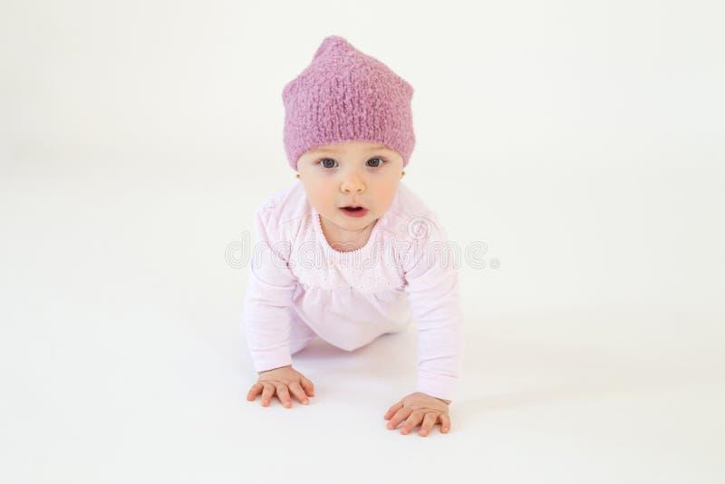 逗人喜爱的小的女婴佩带的帽子坐地板 库存图片
