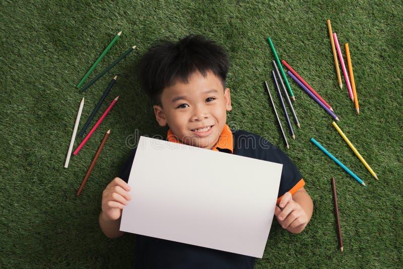逗人喜爱的小的7年男孩图画在说谎的公园在草之外 免版税库存照片