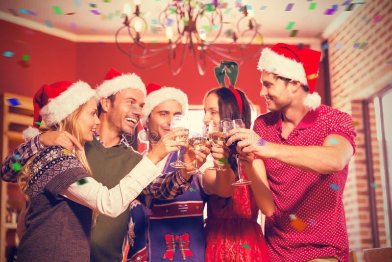 逗人喜爱的小组的综合图象敬酒与圣诞老人帽子的朋友 库存例证