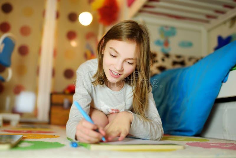 逗人喜爱的少女文字信件在家 做她的家庭作业的孩子在她的屋子里 免版税图库摄影