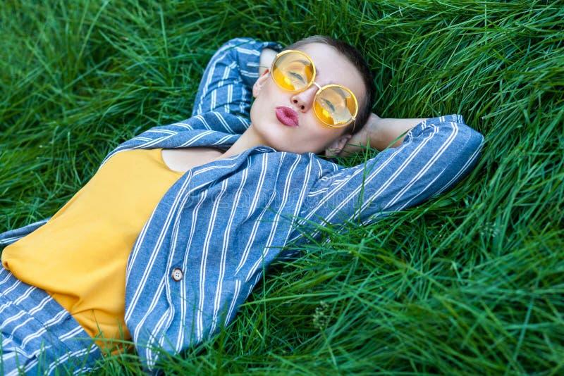 逗人喜爱的少女画象有短发的在偶然蓝色镶边衣服,黄色衬衣,躺下在绿草的玻璃,休息 免版税库存照片