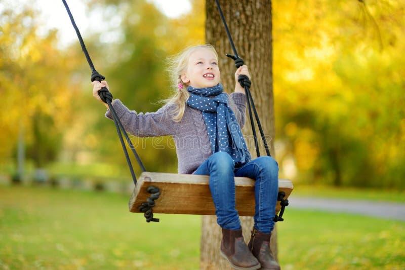 逗人喜爱的少女获得在摇摆的乐趣在晴朗的秋天公园 家庭周末在城市 库存图片