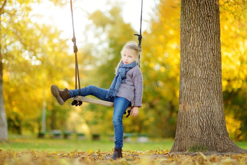 逗人喜爱的少女获得在摇摆的乐趣在晴朗的秋天公园 家庭周末在城市 库存照片