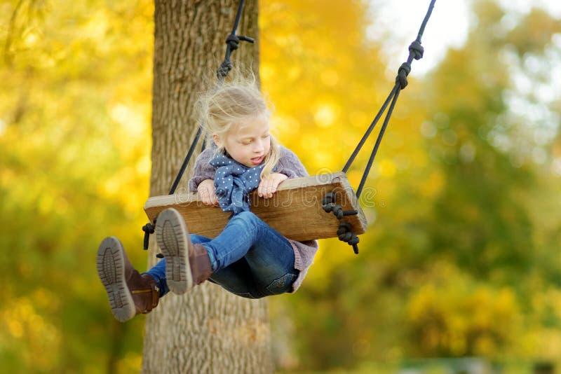 逗人喜爱的少女获得在摇摆的乐趣在晴朗的秋天公园 家庭周末在城市 免版税图库摄影