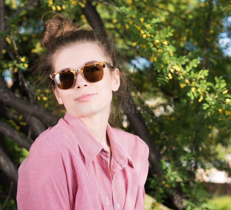 逗人喜爱的少妇佩带的太阳镜户外 桃红色衬衣,被包裹的头发 图库摄影