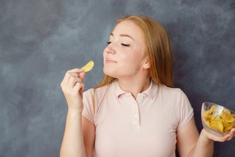 逗人喜爱的少妇喜欢吃土豆片 免版税图库摄影