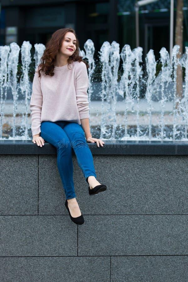 逗人喜爱的少妇获得乐趣在城市的街道上的喷泉旁边 免版税图库摄影