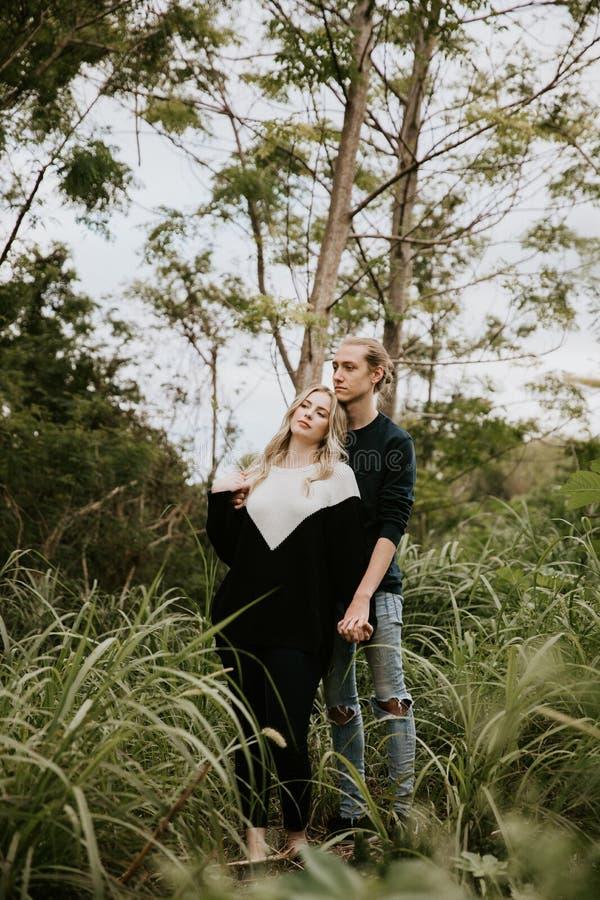 逗人喜爱的年轻人有吸引力的约会在密集的绿色热带森林密林结合看,微笑和笑 免版税库存照片