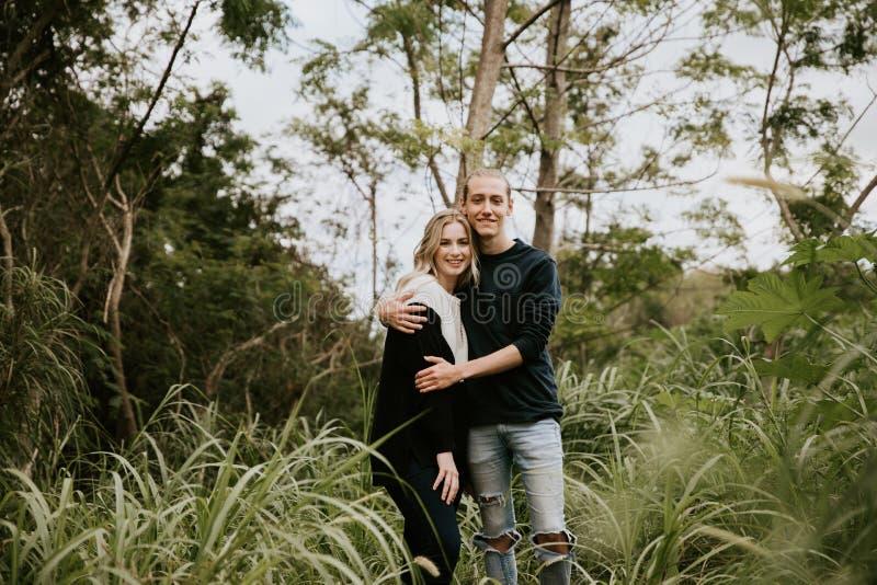 逗人喜爱的年轻人有吸引力的约会在密集的绿色热带森林密林结合看,微笑和笑 免版税库存图片