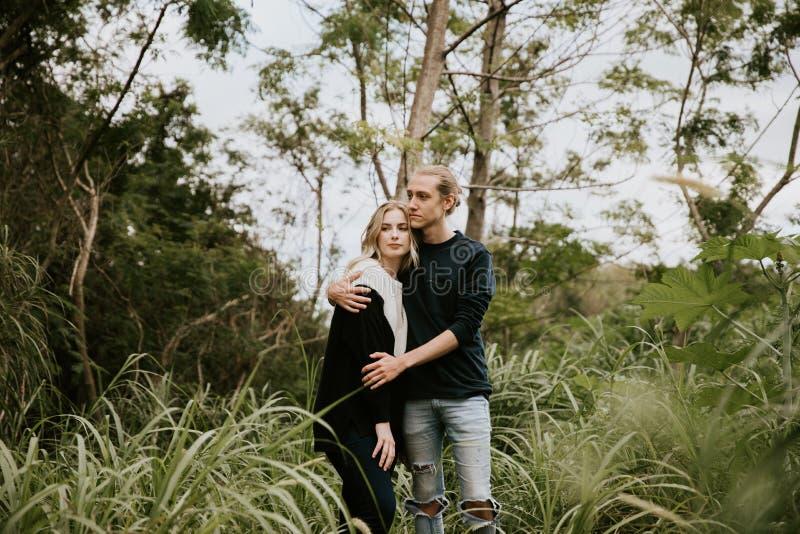 逗人喜爱的年轻人有吸引力的约会在密集的绿色热带森林密林结合看,微笑和笑 库存照片