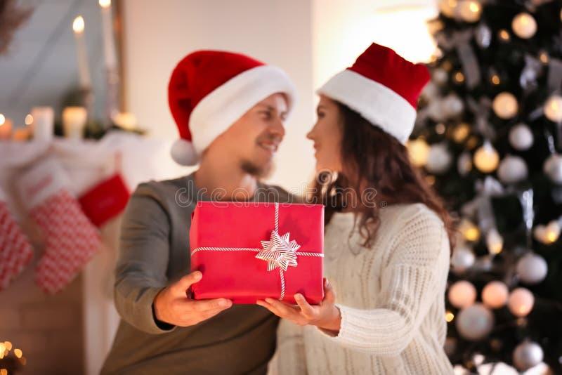 逗人喜爱的年轻加上在圣诞老人帽子和圣诞礼物在家 免版税库存图片