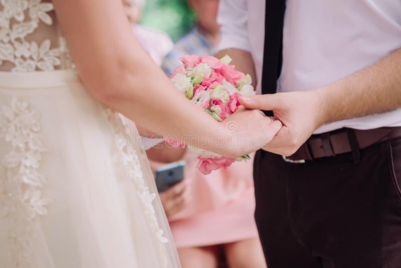 逗人喜爱的年轻夫妇新娘和新郎握他们的手 免版税库存图片