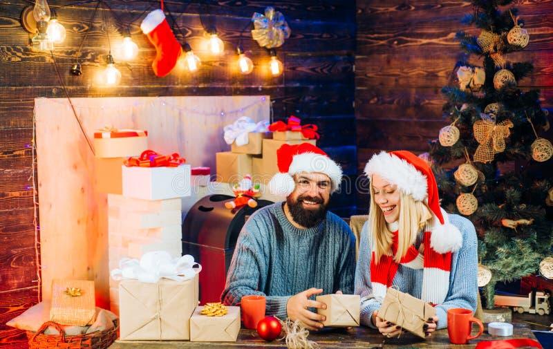逗人喜爱的年轻女人和帅哥有圣诞老人帽子的 爱 与圣诞礼物箱子的新年家庭在前面 库存照片