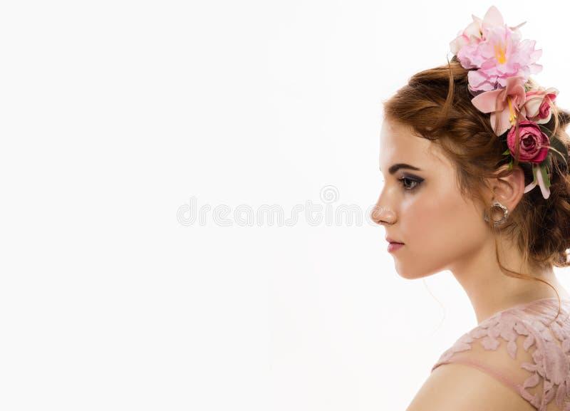 逗人喜爱的年轻女人画象精美桃红色礼服的,与花圈的专业发型 E 库存照片