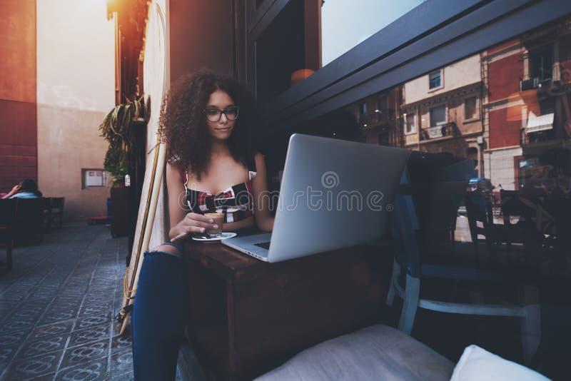 逗人喜爱的年轻女性企业家有卷曲非洲的头发的和镜片的在举行一个杯子可口的一个室外酒吧坐 免版税库存图片