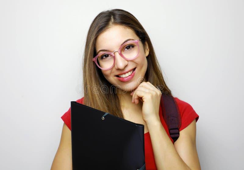 逗人喜爱的年轻学生女孩画象有玻璃、文件夹和背包的 免版税图库摄影