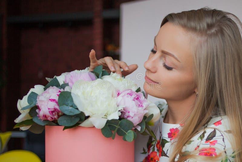 逗人喜爱的年轻白肤金发的妇女嗅花花束  在帽子箱子的精美桃红色牡丹 库存图片