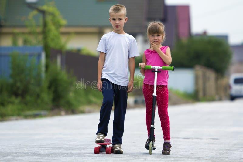 逗人喜爱的年轻白肤金发的孩子、兄弟和姐妹、女孩桃红色衣物的在滑行车和英俊的男孩一起使用的滑板的  免版税图库摄影